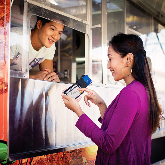 Woman using a mobile card reader to pay at a food truck