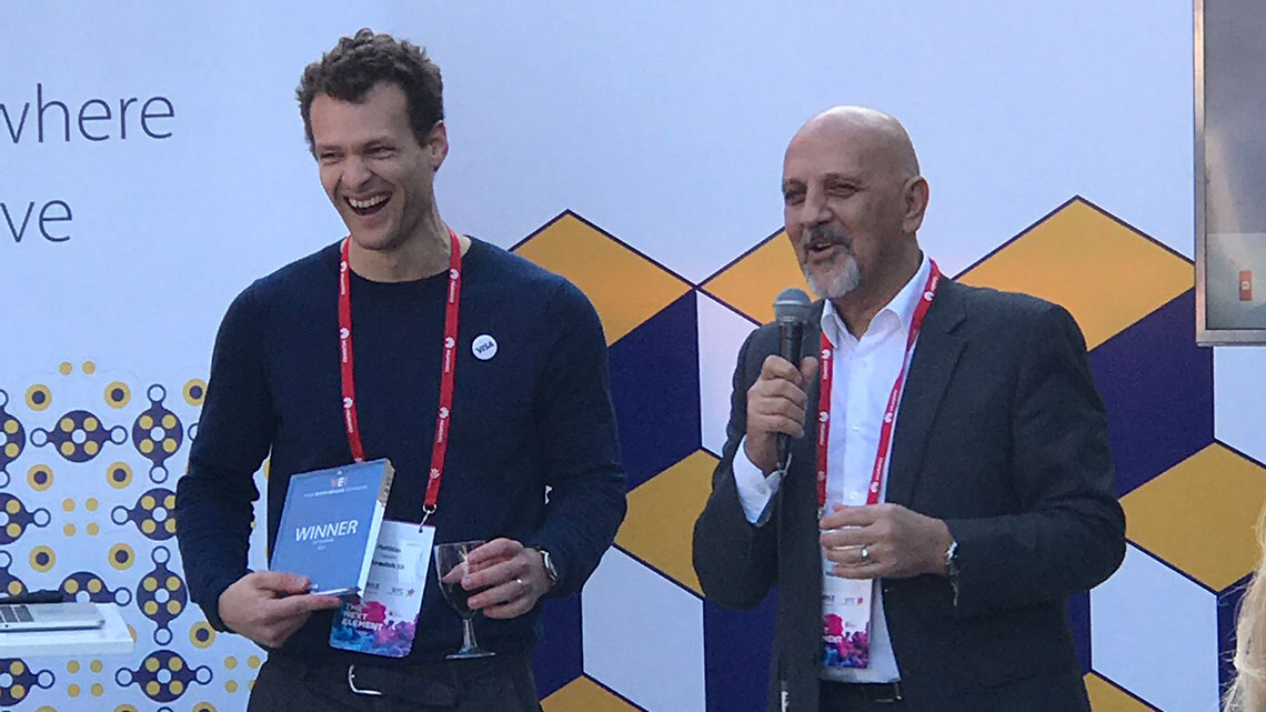 Two men standing next to each other with the man on the left holding an award and the man on the right holding a microphone.